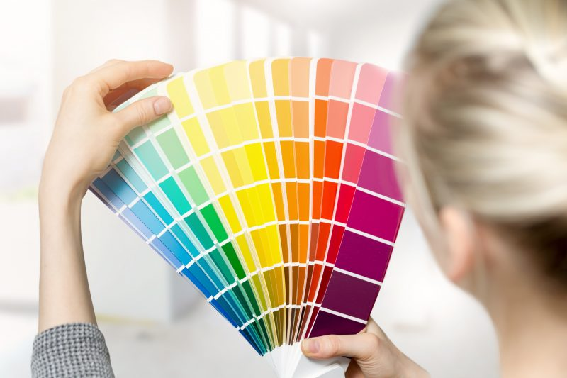 woman selecting home interior paint color from swatch catalog